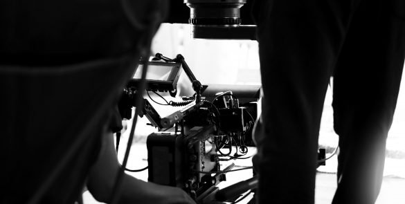 Behind the scenes of video production in studio which filming a online movie with professional set up such as high definition vdo camera, lens, monitor or tripod and crane beside crew team.